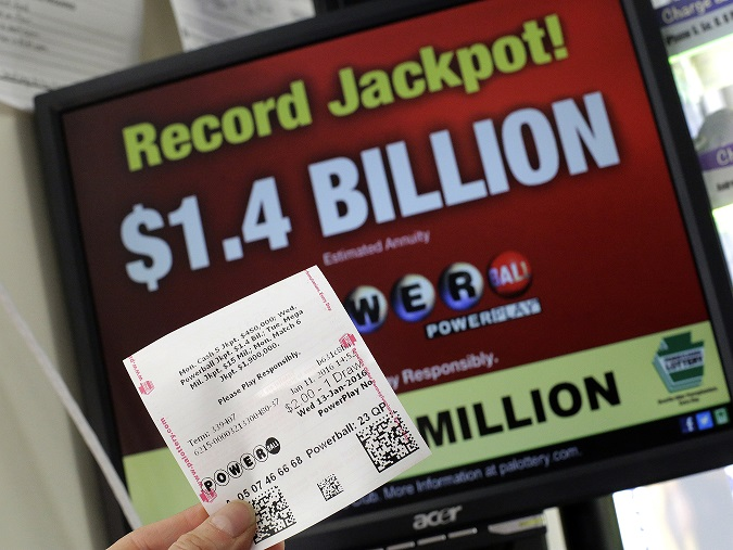 A Powerball ticket purchased in a convenience store in Lancaster, Pa., is held in front of a Pennsylvania Lottery computer screen Monday, Jan. 11, 2016. The Powerball jackpot has grown to over 1 billion dollars. (AP Photo/Gene J. Puskar)