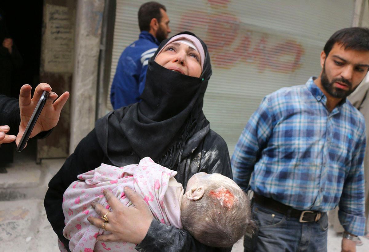 Seorang wanita Syria membawa jenazah bayi nya selepas dia dikeluarkan dari runtuhan bangunan berikutan serangan udara yang dilaporkan di kawasan al-Muasalat di Aleppo - Thaer Mohammed / AFP / Getty Images