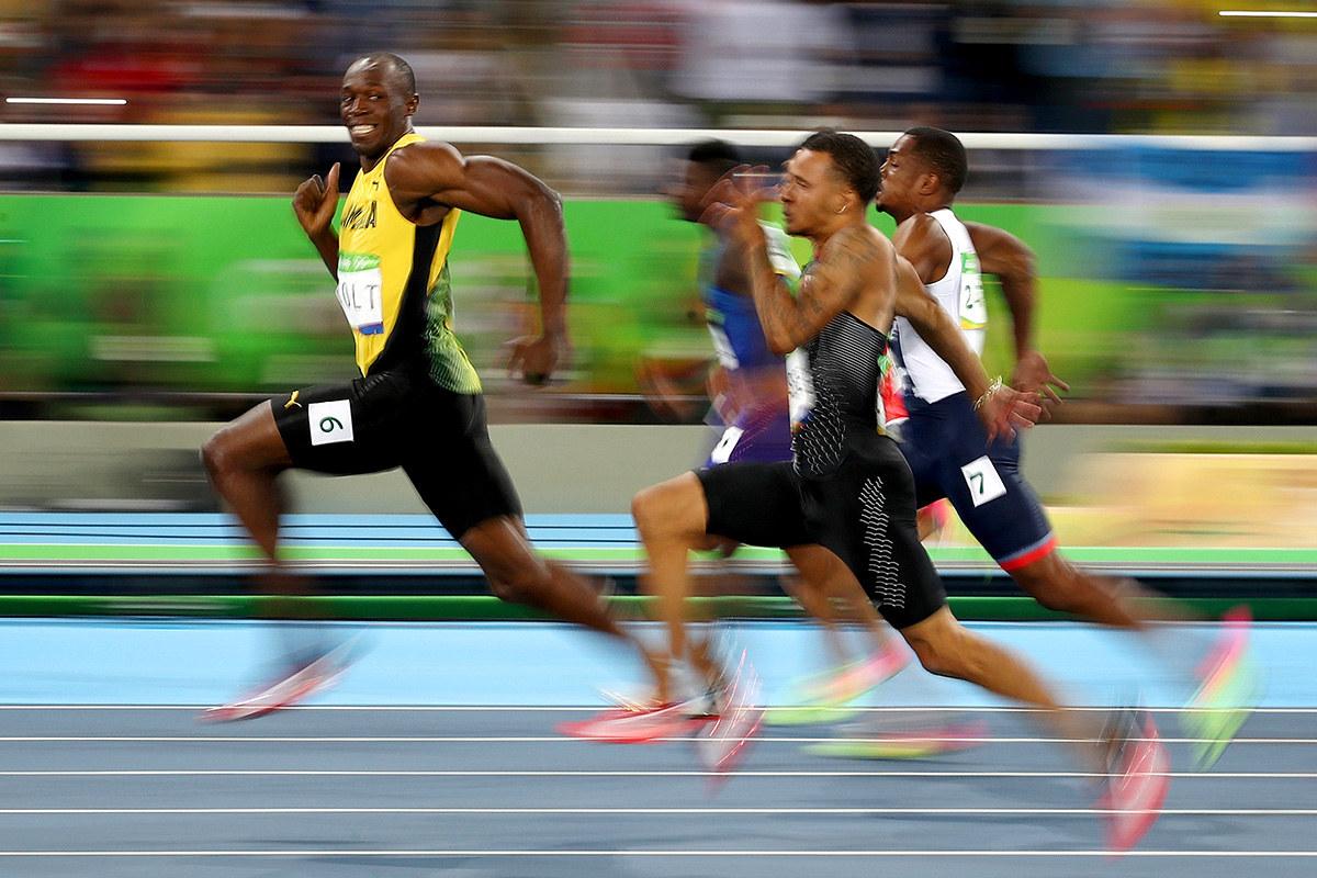 Usain Bolt dari Jamaica sempat tersenyum bersama pesaingnya di Skan Olimpik Rio de Janeiro - Cameron Spencer / Getty Images