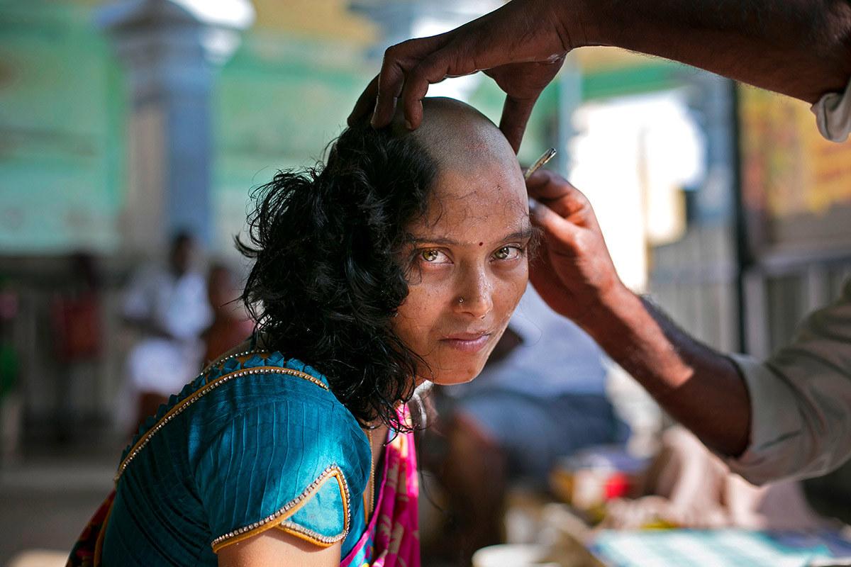 Rupa, 28, mencukur rambut di Kuil Murugan Tiruttani dengan harapan bahawa menderma kepada tuhan-tuhan akan menyembuhkan penyakit anaknya itu. Ia adalah perkara biasa bagi orang yang Hindu untuk mencukur kepala rambut mereka di sebuah kuil - Allison Joyce / Getty Images