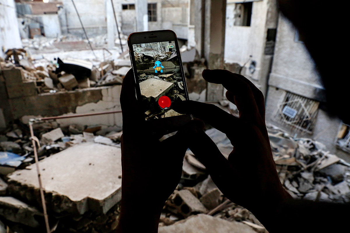 Peminat permainan video di Syria menggunakan aplikasi Pokémon Go pada telefon bimbitnya untuk menangkap Squirtle di tengah-tengah runtuhan. -Sameer Al-doumy / AFP / Getty Images